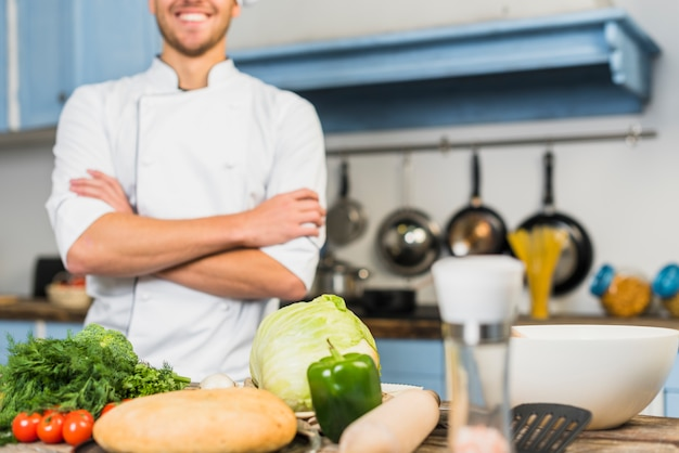 Chef in kitchen in front of vegetables