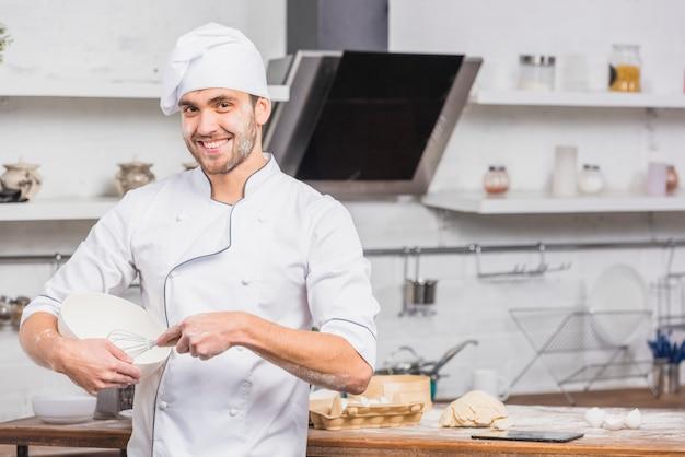 Chef in kitchen making dough