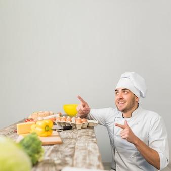 Chef in cucina che punta verso copyspace