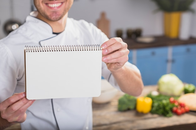 Chef in kitchen showing notepad