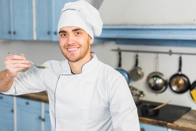 Chef in cucina con un cucchiaio