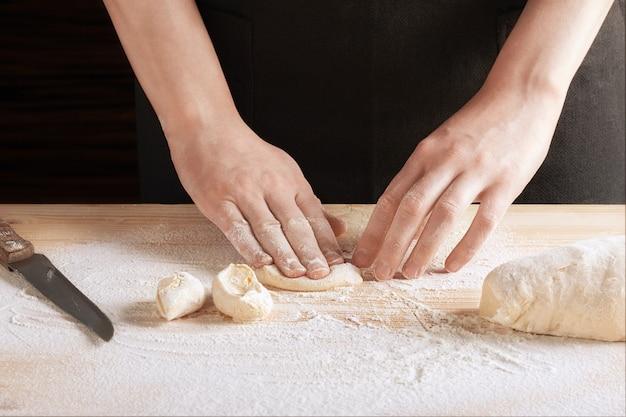 Шеф-повар замешивает ломтик теста на деревянном столе, посыпанном мукой