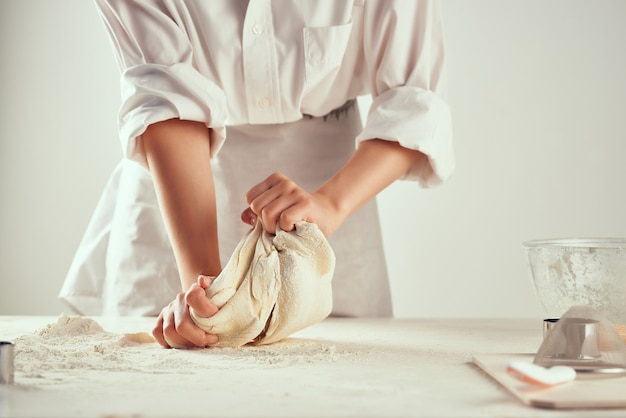 Шеф-повар замешивает тесто на столе профессиональная выпечка на кухне Premium Фотографии