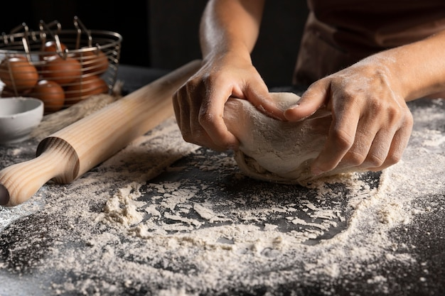 Шеф-повар замешивает тесто в муке на столе