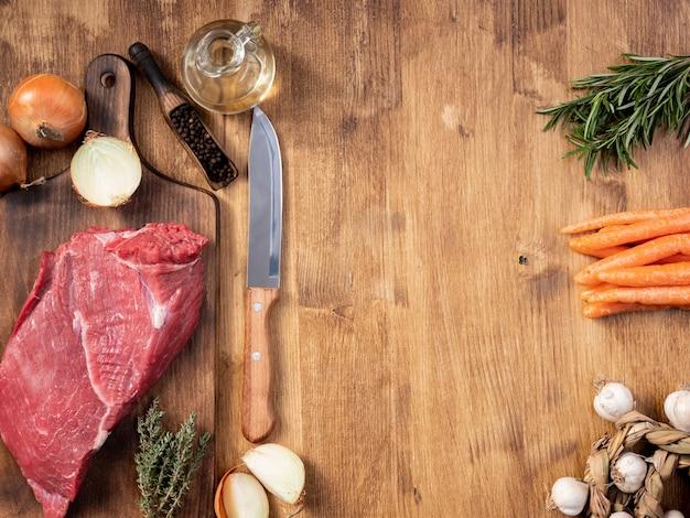 Нож шеф-повара рядом с большим куском свежих овощей красного мяса. деревянная разделочная доска. консервированный чеснок.