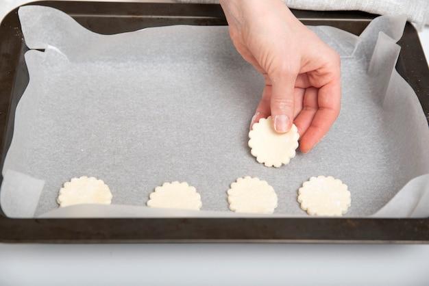 Шеф-повар раскладывает тестовые заготовки на противне с пергаментной бумагой. процесс создания файлов cookie. домашняя выпечка.
