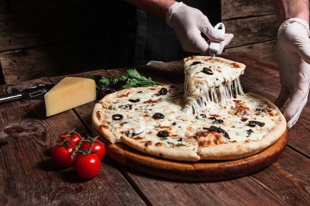 Повар поднимает кусок горячей пиццы с плавящимся сыром. итальянская еда.