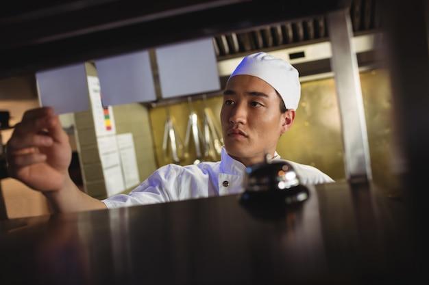 Повар смотрит на список заказов на кухне