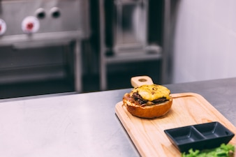 Chef making a beef cheeseburger on wooden plate.