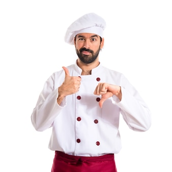 Chef making a good-bad sign over white background