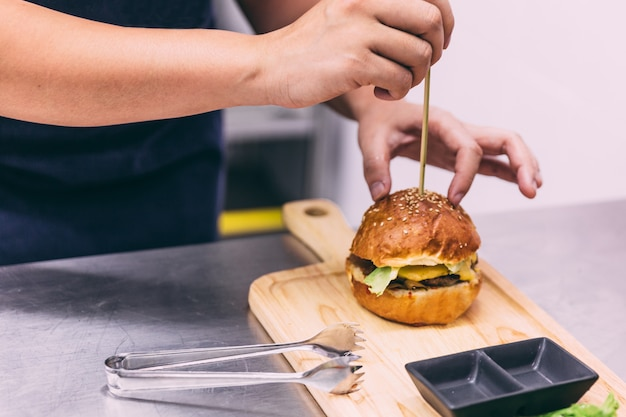 Chef making a beef cheeseburger on wooden plate