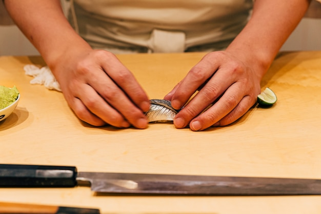 Chef making omakase menu: saba sushi (mackerel) by his hand on wooden kitchen counter. japanese luxury meal.