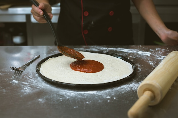 Chef making pizza at kitchen