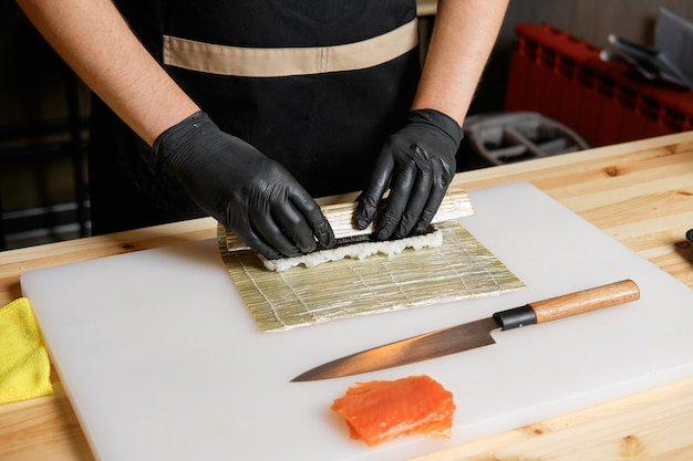 Шеф-повар делает рулетики из лосося