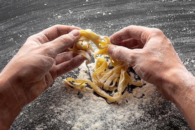 Chef making tagliatelle in flour