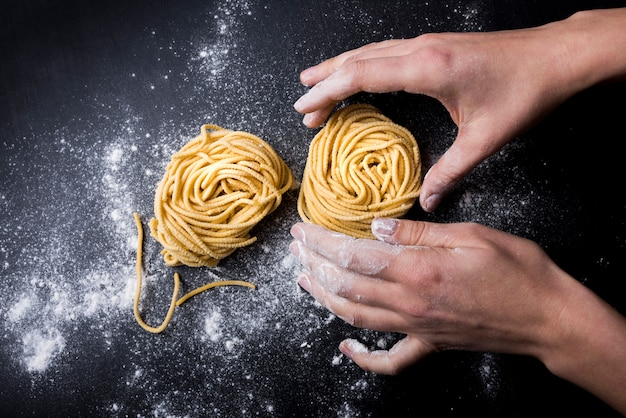 Chef making tagliatelle pasta nest with powder flour on kitchen table