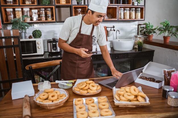 Шеф-повар мужчина готовит пончики на кухне