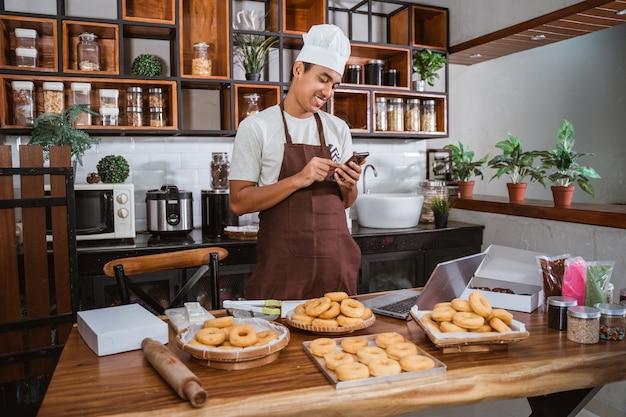 キッチンでドーナツを準備するシェフの男性