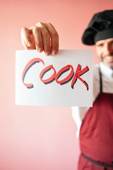 料理人と書かれた看板を持っているシェフの男