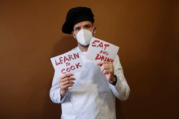 食べると飲むと書かれた看板を持っているシェフの男、彼は彼の顔にマスクを着用しています