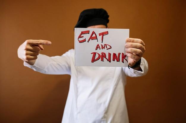 食べて飲むと書かれた看板を持っているシェフの男