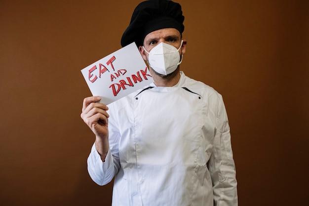 Мужчина шеф-повар держит табличку с надписью