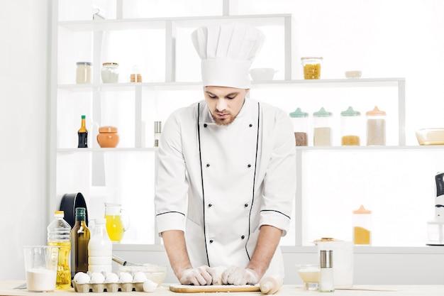 Шеф-повар в униформе замешивает сырое тесто на кухне
