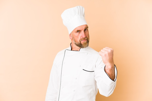 Chef man isolated on beige background showing fist to camera, aggressive facial expression.