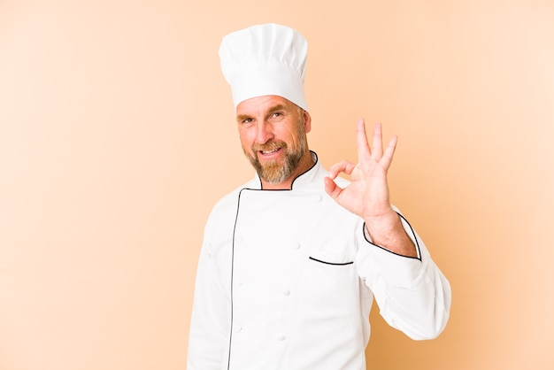Chef man isolated on beige wall cheerful and confident showing ok gesture.