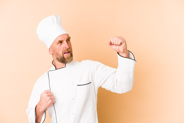 Chef man isolated on beige wall raising fist after a victory, winner concept.