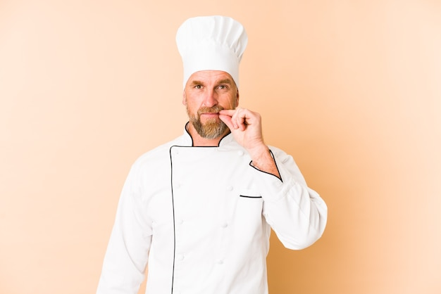 Chef man isolated over beige with fingers over lips keeping a secret.