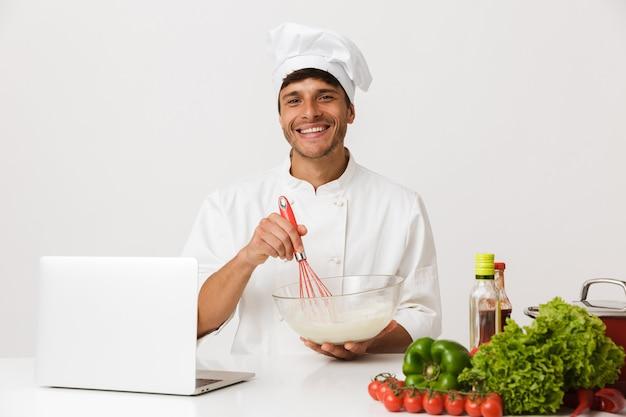 ラップトップコンピューターを使用して白い壁の料理で隔離されたシェフの男。