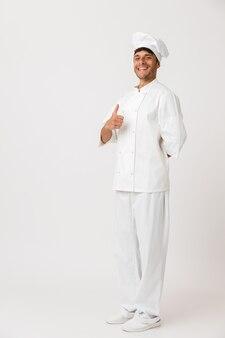 親指を立てて白い壁に孤立したシェフの男。