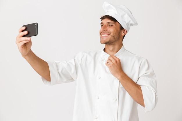 白い壁に隔離されたシェフの男が携帯電話で自分撮りをします。