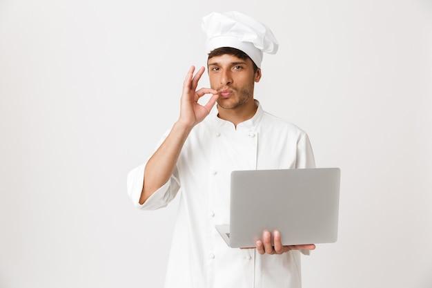 ラップトップコンピューターを使用して白い壁に隔離されたシェフの男。