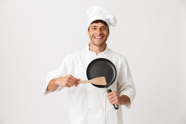 食器を保持している白い壁に孤立して立っているシェフの男。