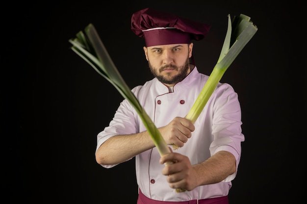 Chef man in uniform holds two leek stalks crossing them like weapon