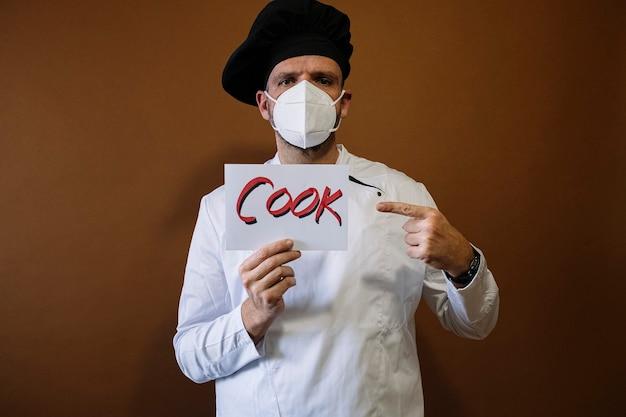 フェイスマスクと料理人と書かれた看板を持つシェフの男