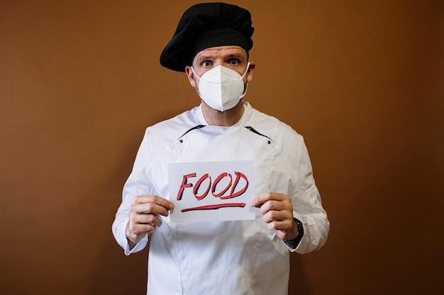 フェイスマスクと食べ物を示す看板を持つシェフの男