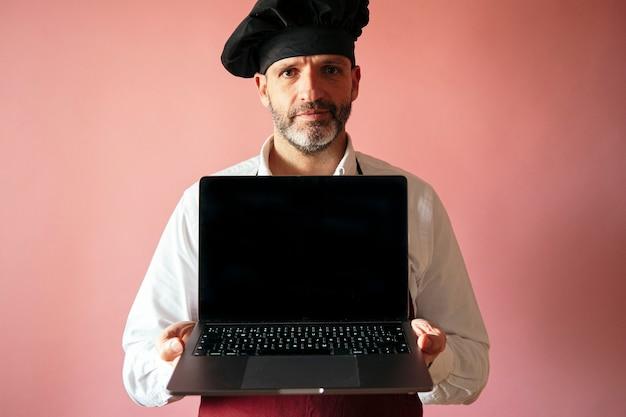 ピンクの壁とラップトップを持つシェフの男