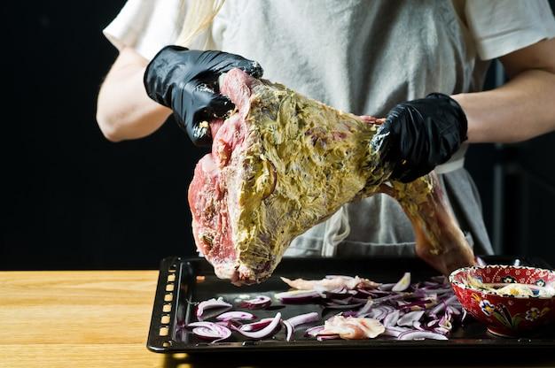The chef marinates the raw leg of lamb.