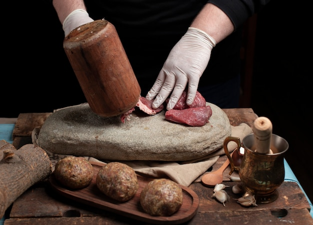 Chef mincing raw meat with wooden hammer on the stone