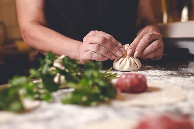 그루지야 어 레스토랑의 요리사가 khinkali를 조각합니다.