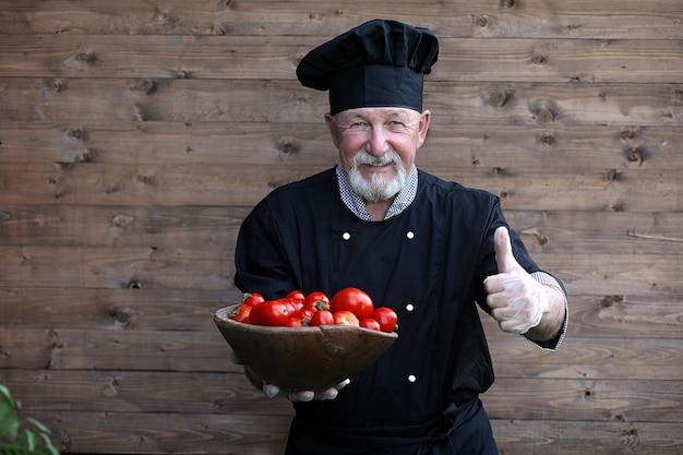 Старый шеф-повар в униформе со свежими овощами на деревянном фоне