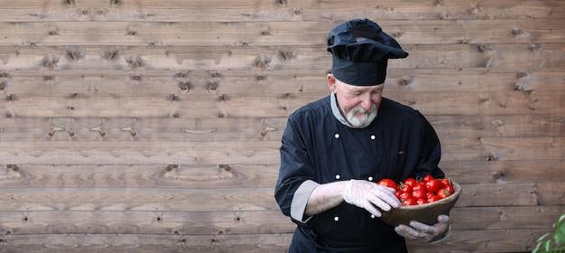 나무 배경에 신선한 야채와 함께 유니폼을 입고 오래 된 요리사