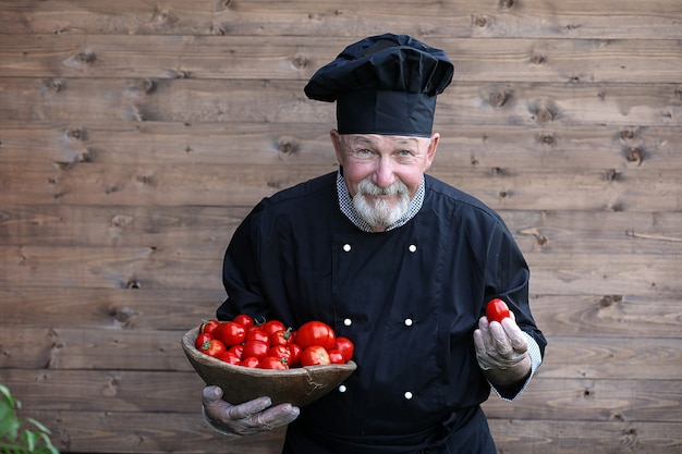 Chef old in uniform with fresh vegetables on a wooden bacground