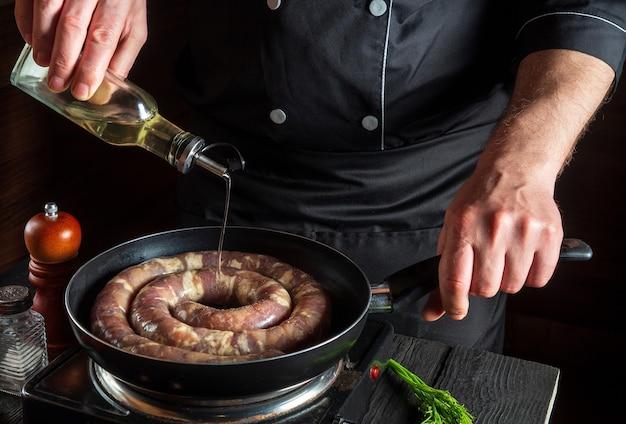 요리사 또는 요리사는 생고기 소시지와 함께 팬에 기름을 추가합니다. 야채와 함께 테이블에 레스토랑이나 카페의 부엌에서 소시지 요리 준비