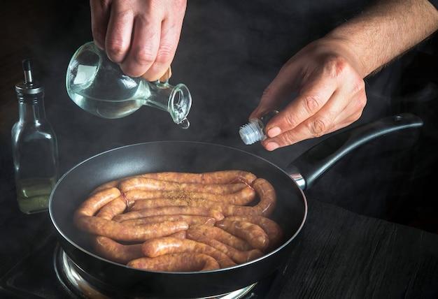 요리사 또는 요리사가 생고기 소시지와 함께 팬에 기름을 추가합니다 부엌에서 소시지 요리를 위한 준비