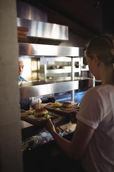 シェフがトレイとフライドポテトとハンバーガーをウェイトレスに渡す