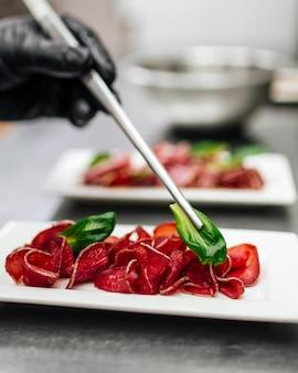 Шеф-повар кладет листья базилика на тарелку с ветчиной прошутто и щипцами